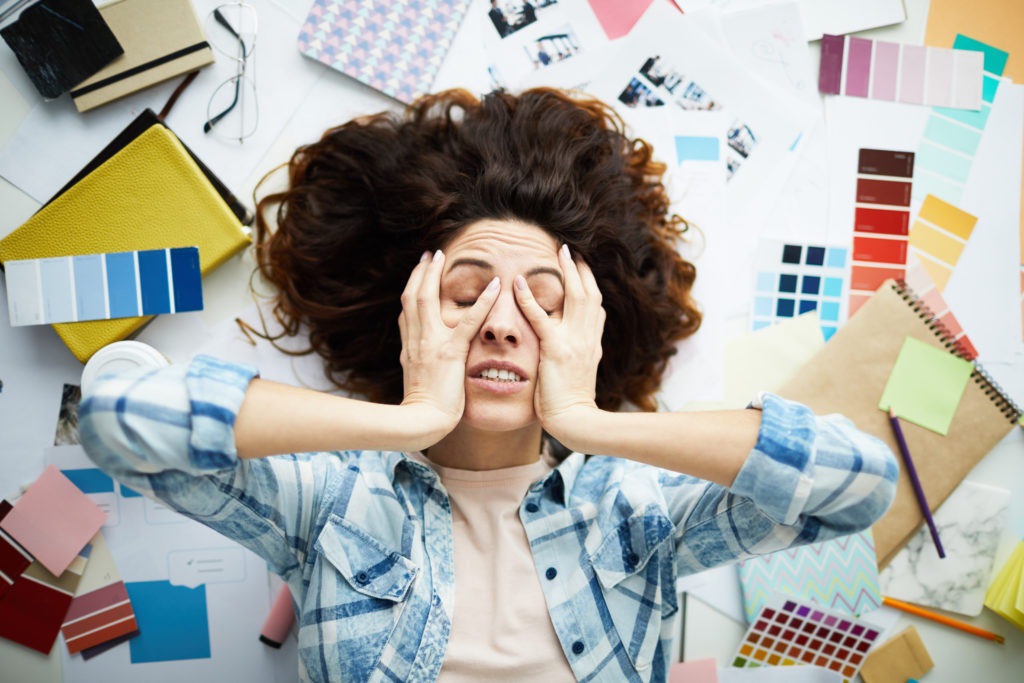 Top view portrait of exhausted designer lying in pile of work with eyes closed, copy space